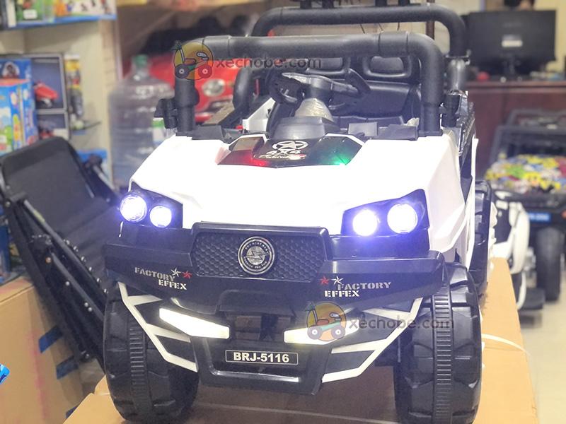 Chiếc xe ô tô điện trẻ em 2 chỗ ngồi này có cụm đèn LED phía trước bền, sáng, khung gầm cao vượt mọi địa hình.